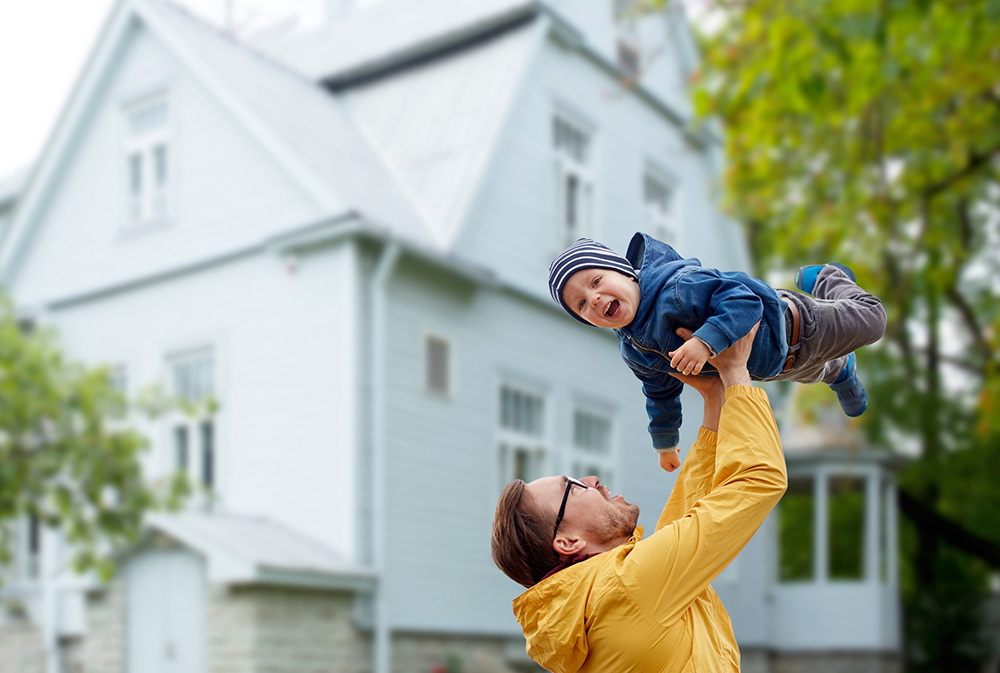 Father holding up his son in front of a historic style home.