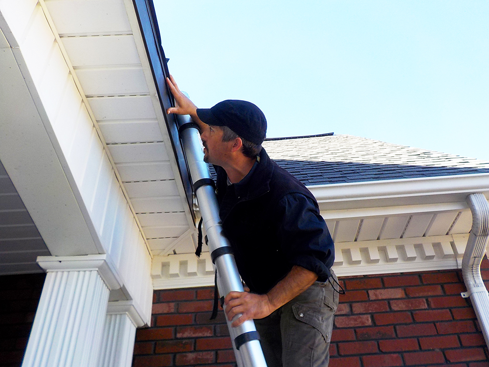 One of Foundations' home inspectors Dayne Withers on a ladder inspecting a roof.