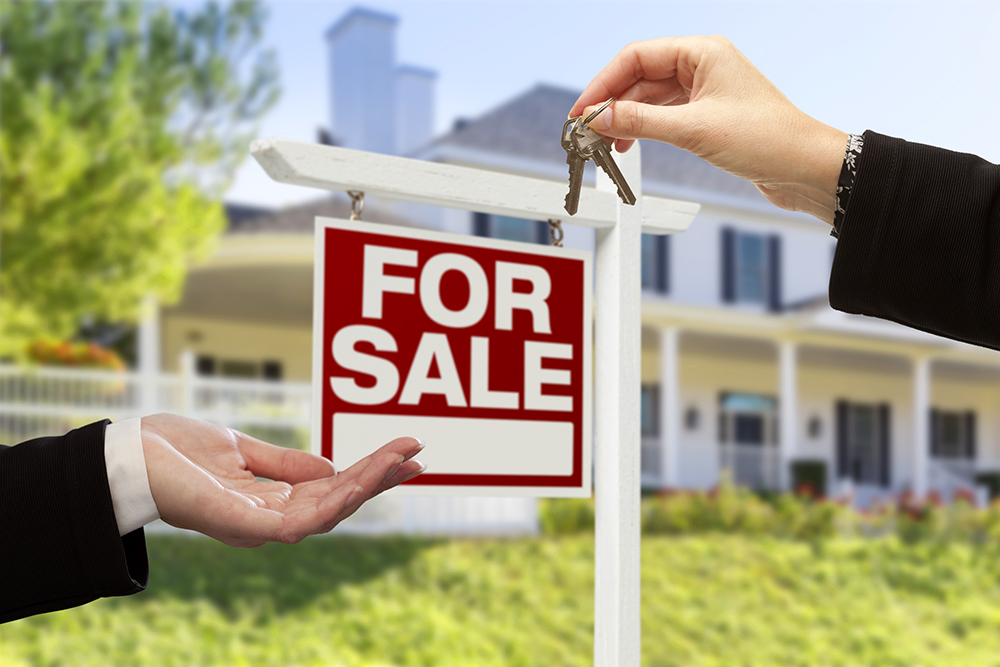 Real Estate Agent Handing Over the House Keys in front of a For Sale sign